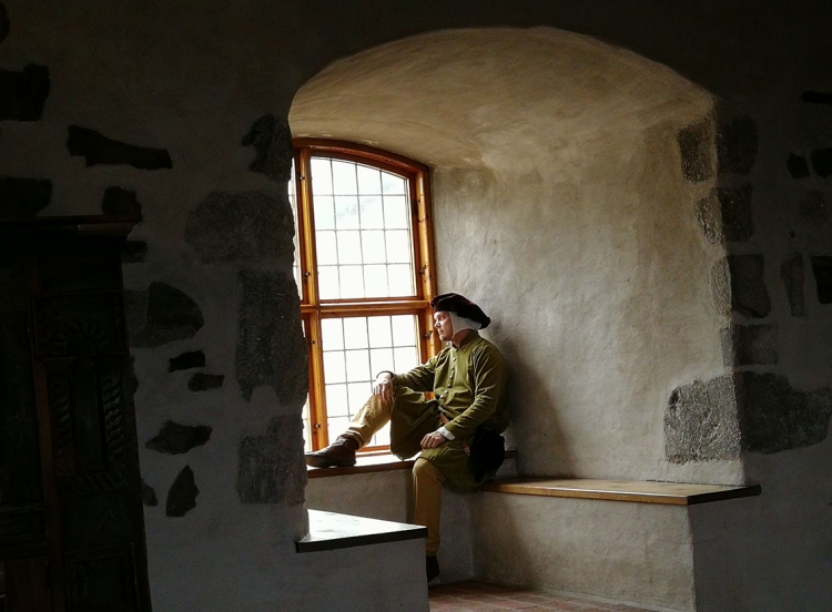 Keskiaikavaatteisiin pukeunut miesoletettu istuu Turun linnan ikkunasyvennyksessä