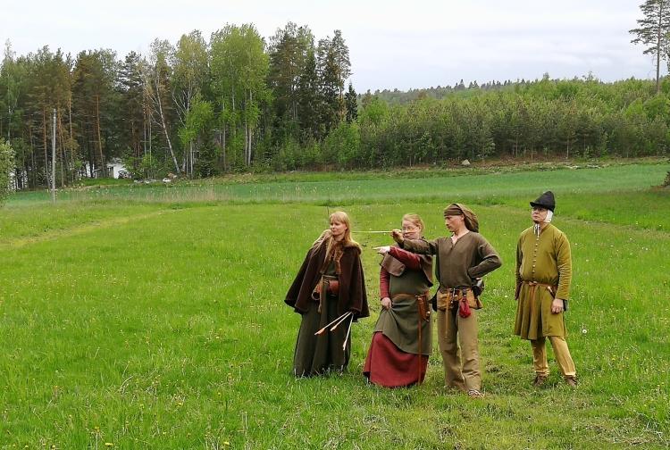 Neljä jousiampujaa pellolla