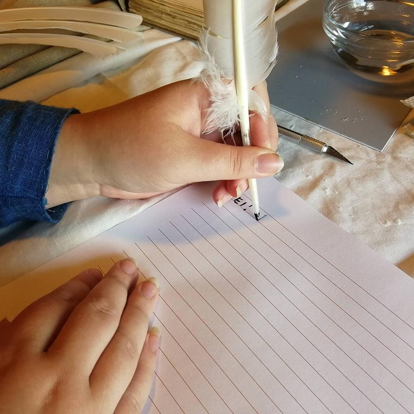 Vasenkätinen henkilö kirjoittaa sulkakynällä ja musteella