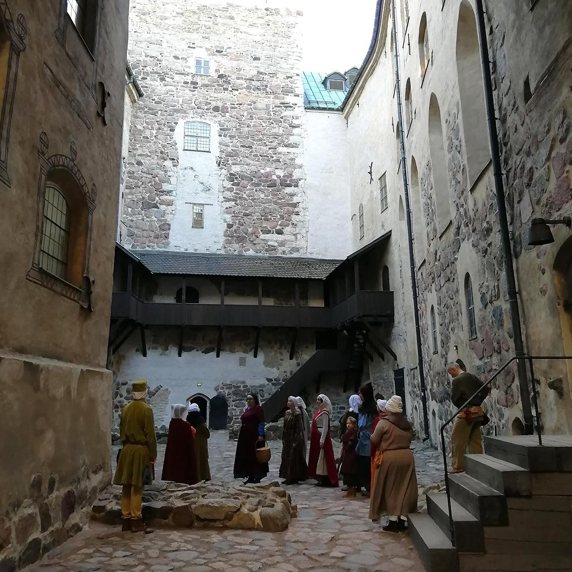 Ryhmä historiallisiin asuihin pukeutuneita harrastajia seisoo Turun linnan sisäpihalla