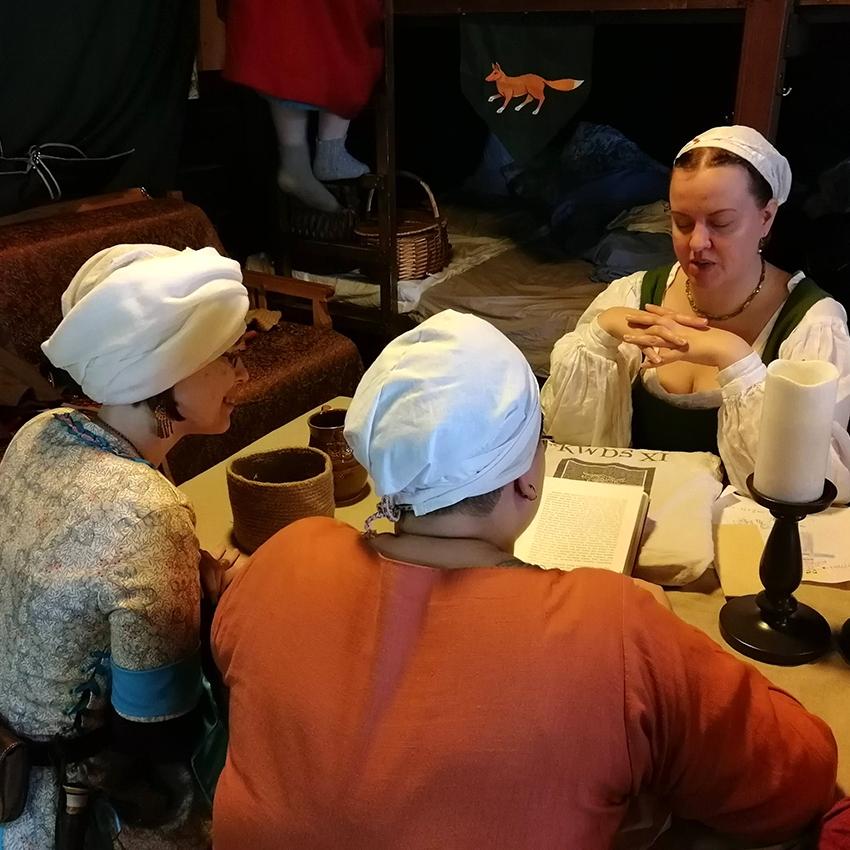 Kolme naisoletettua harrastajaa tutkii pöydän ääressä kirjoja