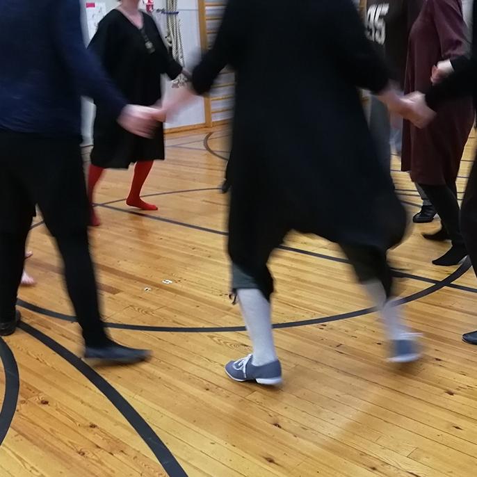 Käsikädessä piirissä laukkaavia tanssijoita liikuntasalissa