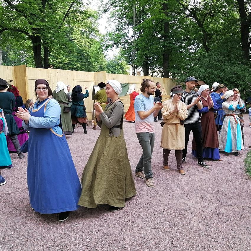 Piiritanssia tanssivia ihmisiä Keskiaikaisilla markkinoilla